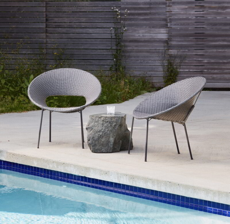 The Ebb boulder is surrounded by two patio chairs beside a pool.