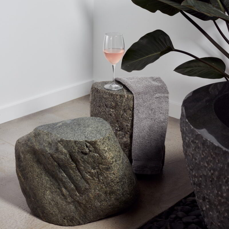 The Ebb boulder on the left and the Ebb column on the right, topped with a wine glass containing pink liquid.
