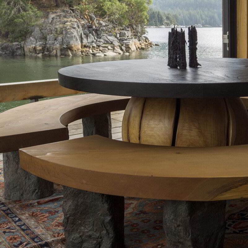 Island dining table and benches with an ocean view.