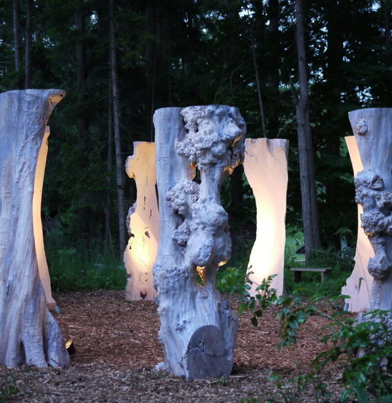 Nine illuminated Sentinel sculptures are pictured installed in a circular formation at the Van Dusen Botanical Gardens.