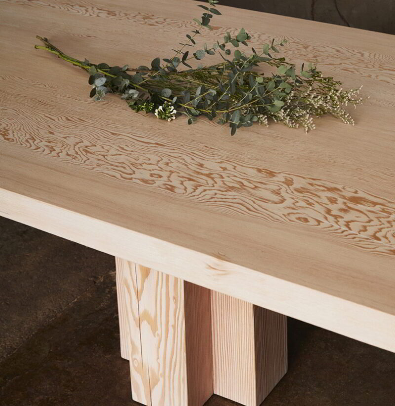 Cropped photo of the Soma Dining Table with decorative eucalyptus.