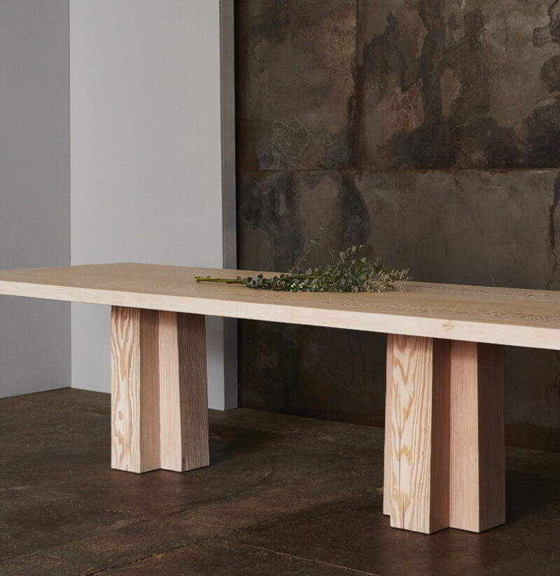 The Soma Dining Table with decorative eucalyptus.