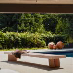 The sweep bench in an outdoor setting with three solid spheres in the background.