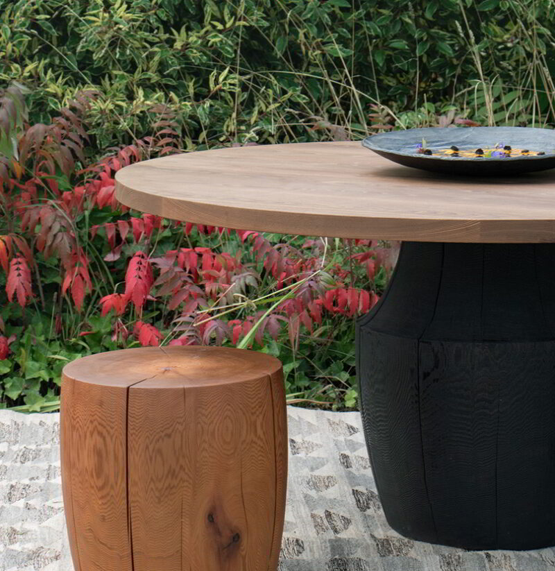The Chelsea table with a scorched base and thermalwood top and the DR-2 in an outdoor setting.