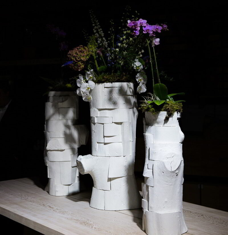Three flower-filled vessels on a Soma Dining table.