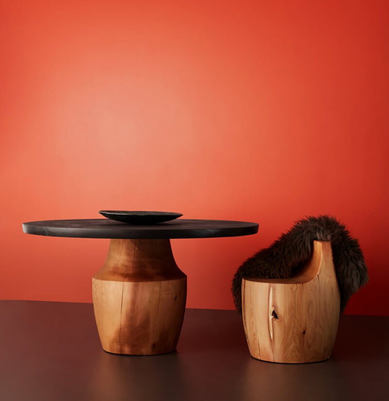 The Chelsea stool and table are pictured against a red background.