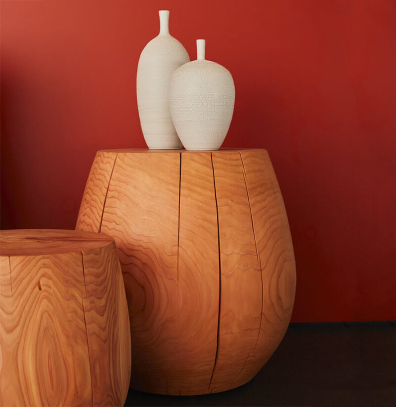 Two t-cups decorated with white ceramic vases are pictured against a red wall.
