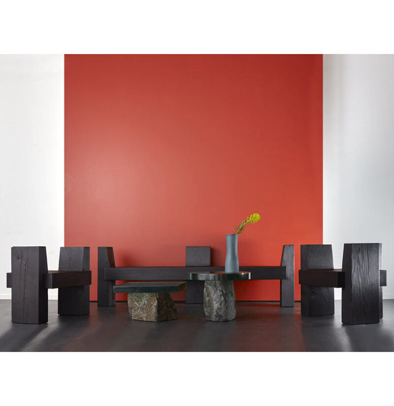 The beton brut bench chairs are pictured against a red background. They are surrounding two flow side tables.