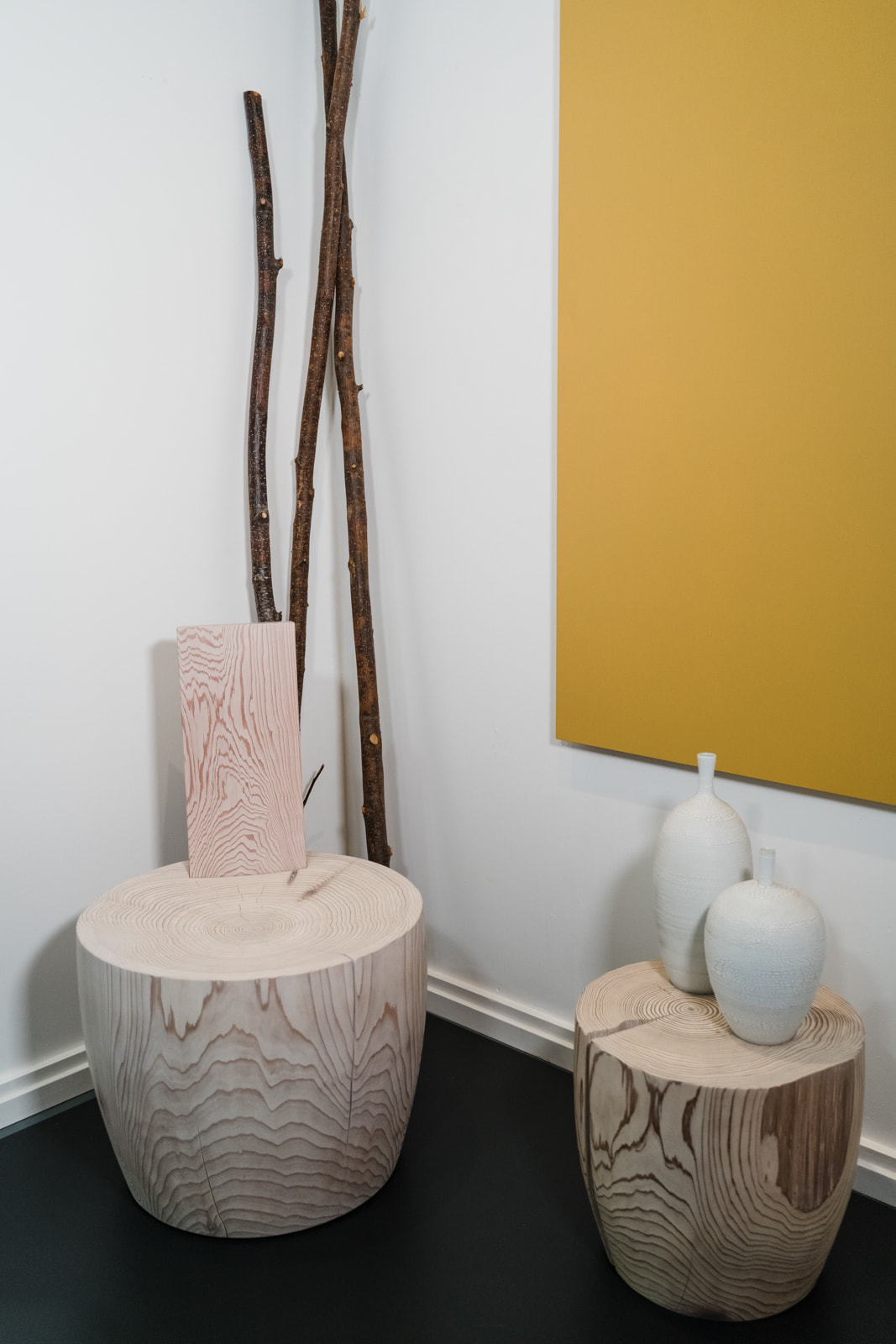 Mysa chair and DR-2T side table with a yellow wall hanging. There are white vases on the side table and decorative branches in the background.